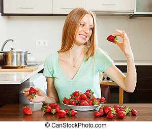 Positive woman eating strawberry in home - Positive blonde...