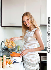 Happy pregnant housewife cooking - pregnant woman cooking...