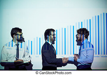 Congrats - Happy young businessmen handshaking by chart of...