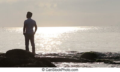 silhouette of young guy stands on rocks in sea