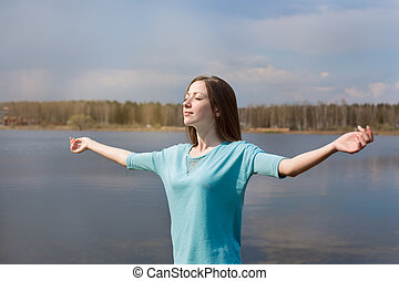 Girl with closed eyes smiling to sun