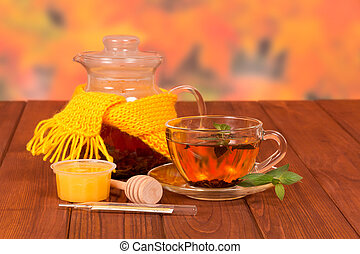 Scarf and a cup of tea - Teapot tied with yellow scarf and a...