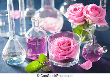 alchemy and aromatherapy set with rose flowers and chemical...