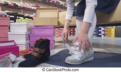 Child trying on new silver sneakers for girls in children shoe store