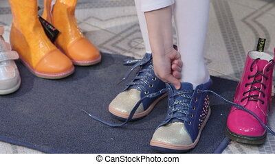 Child choosing and trying on new shoes for junior girls in...