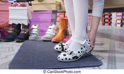Little girl choosing and trying on new  flat shoes in children shoe store