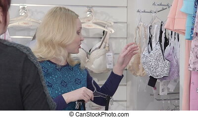 Woman shopping for pregnancy clothes in baby and maternity...
