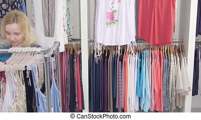 Woman looking for summer clothes in a clothing store pan shot