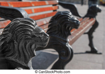 park bench with cast iron legs in the form of a lions head -...