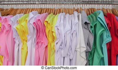 Dolly: Colorful t-shirts on hangers in a clothing store