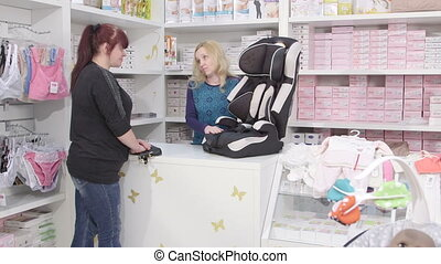 Sales clerk helps the customer to choose infant car seat for...