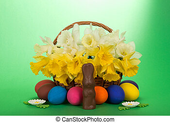 White and yellow narcissuses in a wattled basket, eggs,...