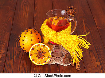 Glass of mulled wine on napkin and orange