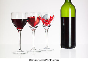 Wine glasses with red wine, heart and golf ball on white...