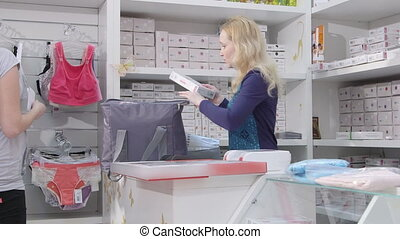 Young pregnant woman buying pregnancy hospital bag and clothes for newborn in baby and maternity shop