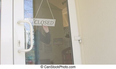 Woman business owner turning sign from closed to open on...