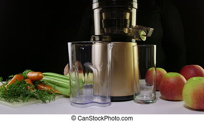 Making freshly squeeze juice from carrots and celery using...