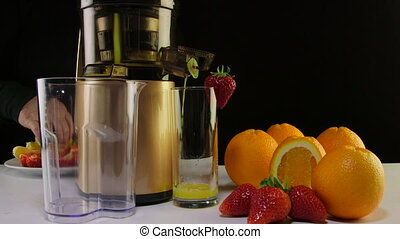 Dolly: Making fresh fruit juice from strawberry and orange using masticating juicer