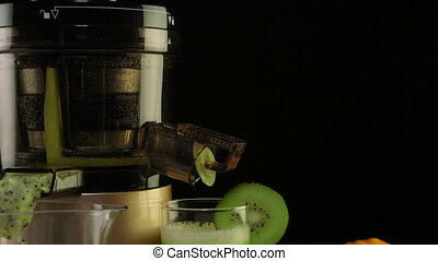 Dolly: Glass of freshly squeezed fruit juice from orange and kiwi using masticating juicer