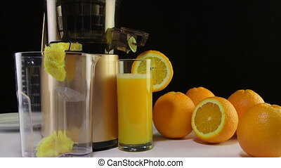 Dolly: Fresh squeezed orange juice with cold press juicer on a black background