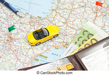 wallet, pen and yellow car on map of Europe