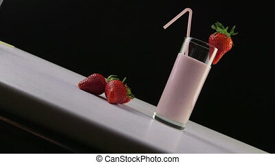 Dolly: Glass of tasty drink with milk and strawberry on black background