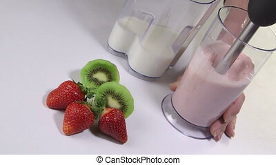 Woman making kiwi strawberry smoothie drink using stick hand...