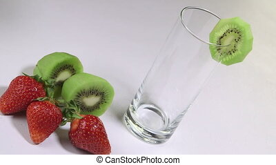 Female hand pouring into a glass fresh kiwi strawberry...