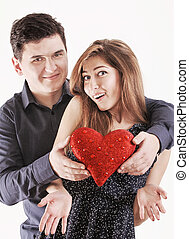 Happy young funny couple with red heart