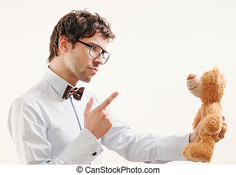 Portrait of serious handsome man scolding teddy bear -...