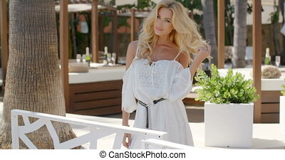 Blond Woman Wearing White Dress Looking on Patio