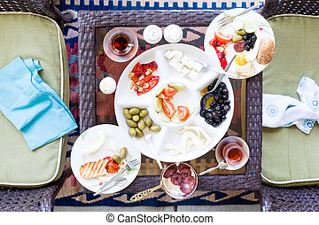Unfinished Turkish breakfast on a patio table with a serving...