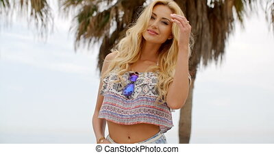 Blond Woman Wearing Crop Top in front of Palm Tree
