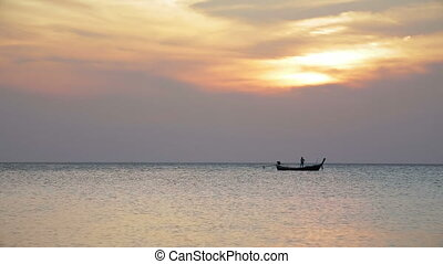 Sunset with a man on fishing boat - Fishing boat on a...