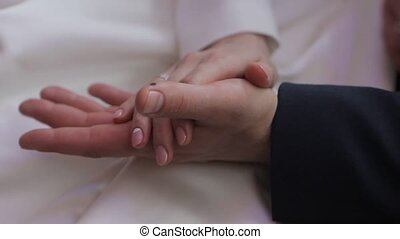 Gently connected hands of a newly-married couple with...
