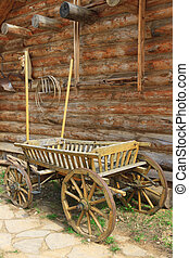 Old cart near the wall - Old wooden cart in the yard of a...