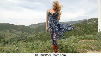 Blond Woman Wearing Dress on Hill near Wind Farm - Full...