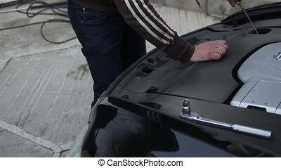 technician checks the oil level in the car