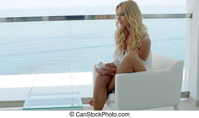 Blond woman on the balcony of a luxurious hotel