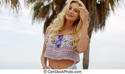 Blond Woman Wearing Crop Top in front of Palm Tree - Waist...