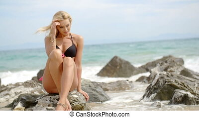 Blond Woman in Bikini Sitting on Boulder on Beach - Full...