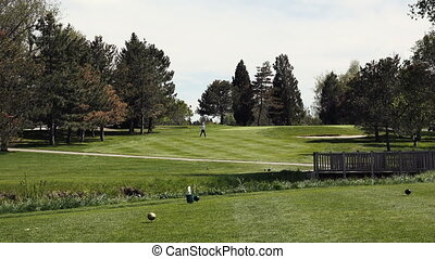Man Walking Up to Golf Green - Golf course video captured at...