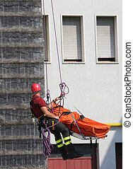 Fireman during an exercise carries the stretcher with the dummy