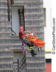 fireman during an exercise carries the stretcher with the climbing rope