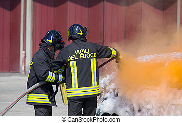 two firefighters in action with foam to put out the fire of...