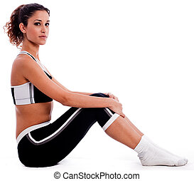 Young woman in fitness outfits sitting on the floor
