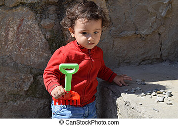 boy 2 years in the red sweater plays with stones and rake