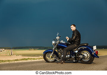 Man sitting on motorcycle on the country road