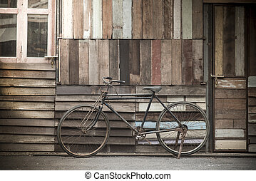 Vintage Bicycle standing near a vintage wood wall.