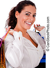 Happy young woman holding shopping bag  in both hands